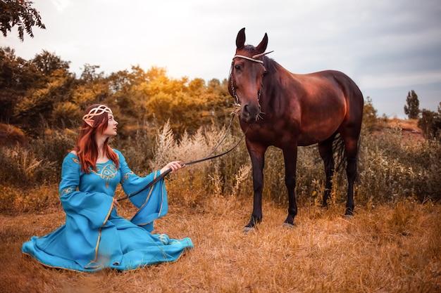 Красивая молодая эльфийка с длинными темными волнистыми волосами гладит свою лошадь, отдыхающую в лесу лесная нимфа гладит свою лошадь забота домашнее животное любовь животных гармония заботливая хозяйка нежное существо миф Premium Фотографии