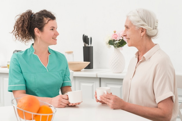 Beautiful young female nurse having coffee with senior woman Free Photo