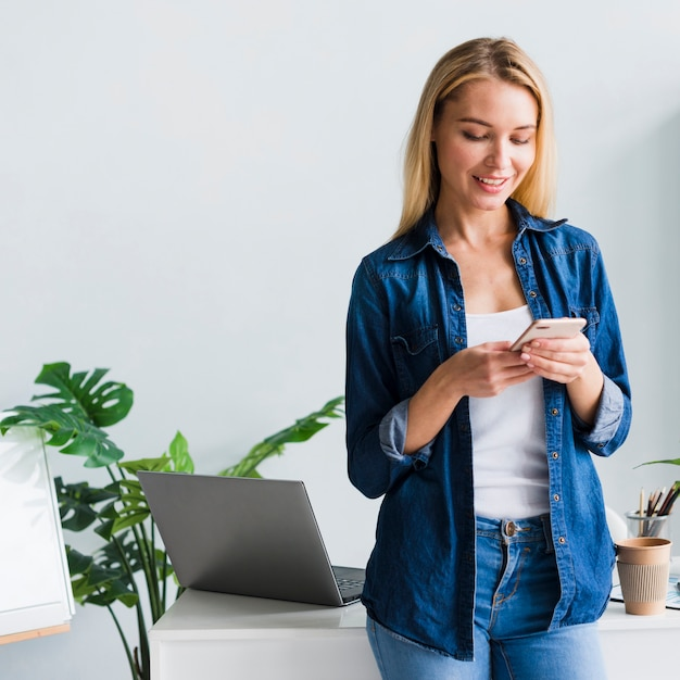 Beautiful young female using smartphone in office Free Photo