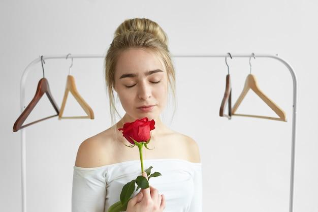 Красивая молодая женщина с пучком волос и обнаженными плечами позирует с пустыми вешалками, с закрытыми глазами, наслаждаясь сладким свежим ароматом, исходящим от красной розы в ее руках Бесплатные Фотографии