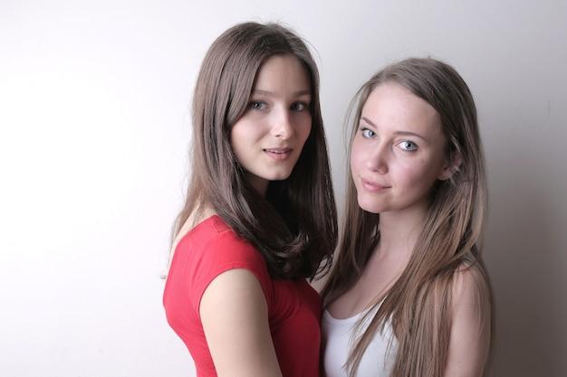 白い壁に立っている美しい若い女性 無料写真