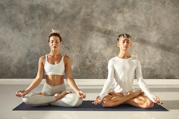 Bella giovane femmina e maschio muscoloso in forma pratica meditazione insieme nella posa del loto, seduto su una stuoia in palestra con muro grigio copyspace, tenendo gli occhi chiusi e tenendosi per mano in mudra Foto Gratuite