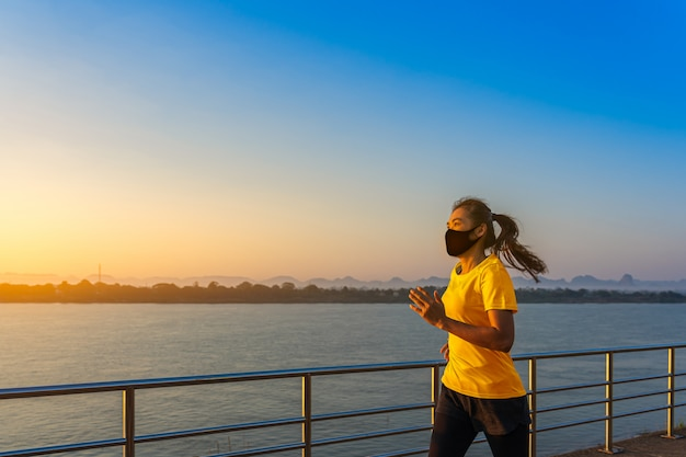 Beautiful young fitness asian woman running and exercise wearing a protective mask at the riverwalk in the morning. Premium Photo
