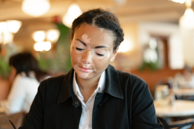A beautiful young girl of african ethnicity with vitiligo sitting in a restaurant Premium Photo