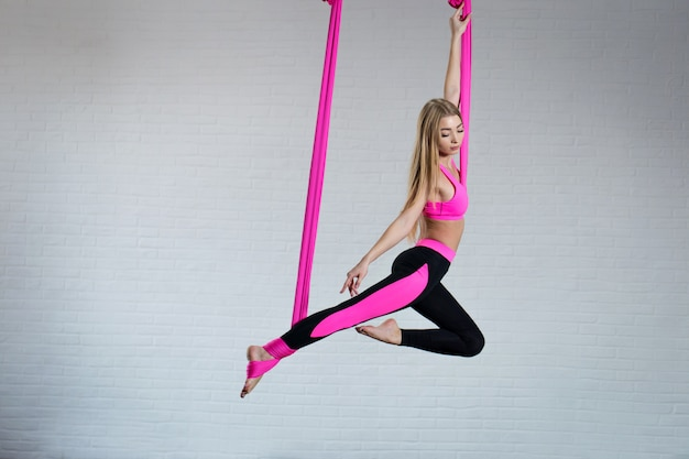 Beautiful young girl antigravity yoga on a pink silk hammock while doing. Premium Photo
