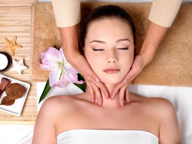 Bella ragazza che ottiene massaggio per il collo nel salone della stazione termale Foto Gratuite