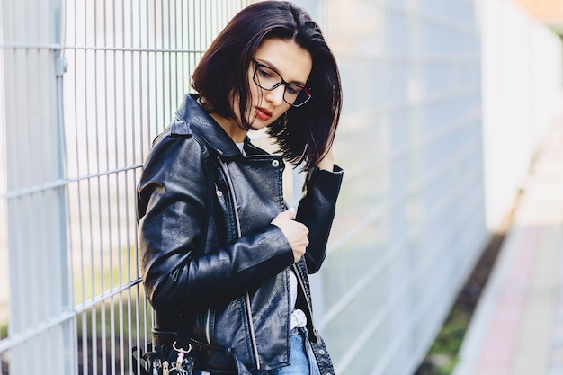 Beautiful young girl in glasses in stylish clothes on light background Premium Photo