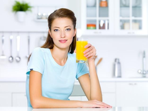 美しい少女は新鮮なオレンジジュースのグラスを保持します。 無料写真