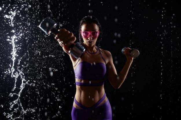 Красивая маленькая девочка в фиолетовой sportswear представляет с гантелями в студии aqua. капли воды распространились по ее телу. идеальная фигура на фоне брызг воды Premium Фотографии