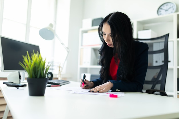 Beautiful young girl is working with documents in the office at the table. the girl highlights important points in the document with a pink marker. Premium Photo