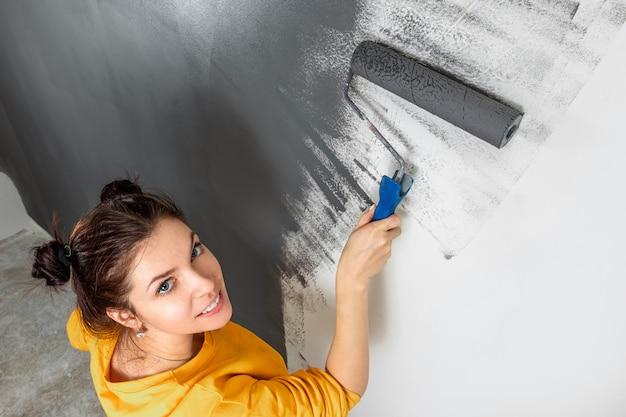 美しい少女は、ローラー、灰色の塗料で黄色のジャケットの壁をペイントします。修理、変更、デザイン、インテリアの概念。 Premium写真