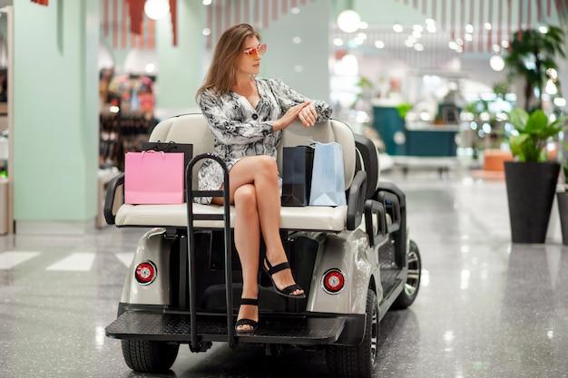 Красивая маленькая девочка представляя пока сидящ с хозяйственными сумками которые стоят на автокресле для транспортировать людей к молу. она смотрит ее часы и проверяет время. день скидок. Premium Фотографии