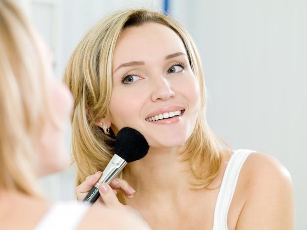 美しい少女は、メイクアップ用のブラシを使って顔にパウダーを塗ります-屋内 無料写真