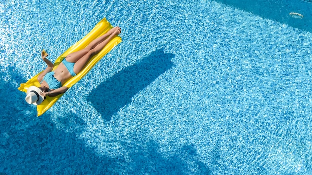 Beautiful young girl relaxing in swimming pool, swims on inflatable mattress and has fun in water on family vacation, tropical holiday resort, aerial drone view from above Premium Photo