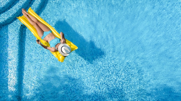 Beautiful young girl relaxing in swimming pool, woman on inflatable mattress, aerial view Premium Photo
