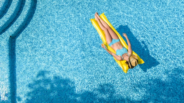 Beautiful young girl relaxing in swimming pool, woman swims on inflatable mattress and has fun Premium Photo