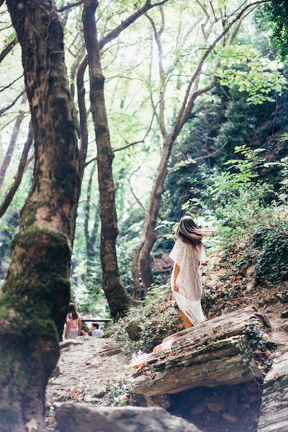 Beautiful, young girl walks at the foot of the mountain along Free Photo