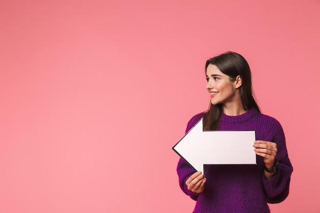 복사 공간에서 멀리 화살표로 가리키는 핑크 이상 격리 서 스웨터를 입고 아름 다운 젊은 여자 프리미엄 사진