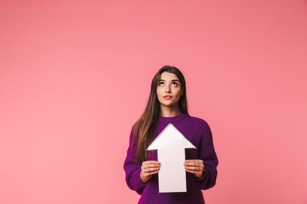 복사 공간에서 위쪽 화살표를 가리키는 핑크 이상 격리 서 스웨터를 입고 아름 다운 젊은 여자 프리미엄 사진
