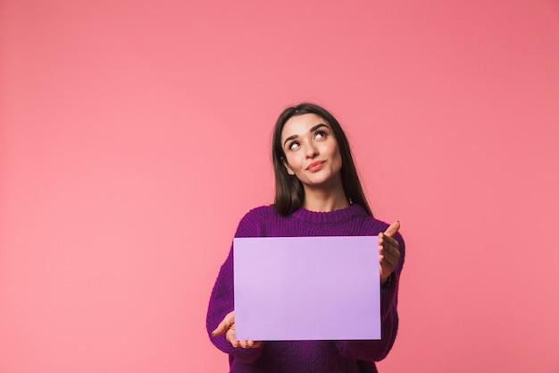 빈 보드를 보여주는 핑크 이상 격리 서 스웨터를 입고 아름 다운 젊은 여자 프리미엄 사진