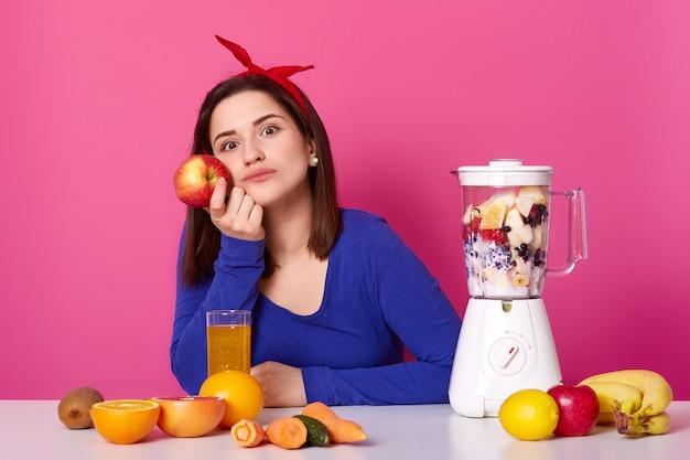 美しい少女は青いセーターを着ており、赤いヘアバンドがテーブルに座って彼女の計画について考えています Premium写真