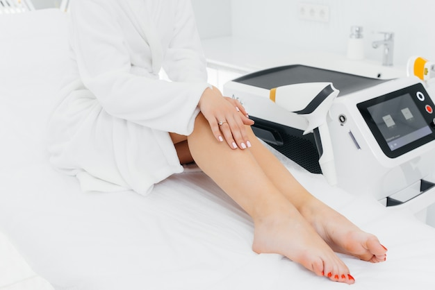 A beautiful young girl will undergo laser hair removal with modern equipment in a spa salon. beauty salon. body care. Premium Photo