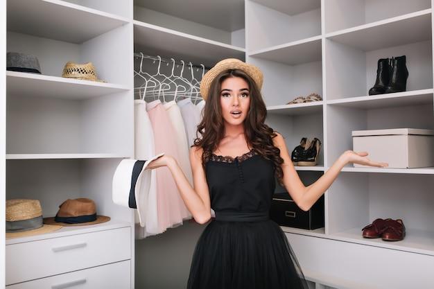 Красивая молодая девушка с каштановыми длинными вьющимися волосами в соломенной шляпе пытается выбрать, что надеть. большой роскошный гардероб. модель имеет модный вид, одетая в элегантное черное платье. Бесплатные Фотографии