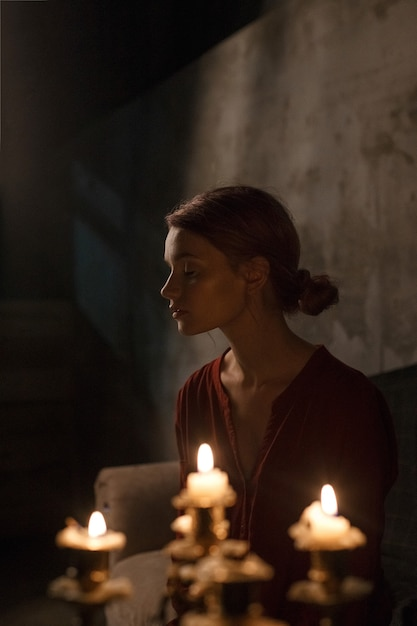 Beautiful young girl with closed eyes in red shirt sitting in gloomy dark room in front of candles in candelabrum Premium Photo