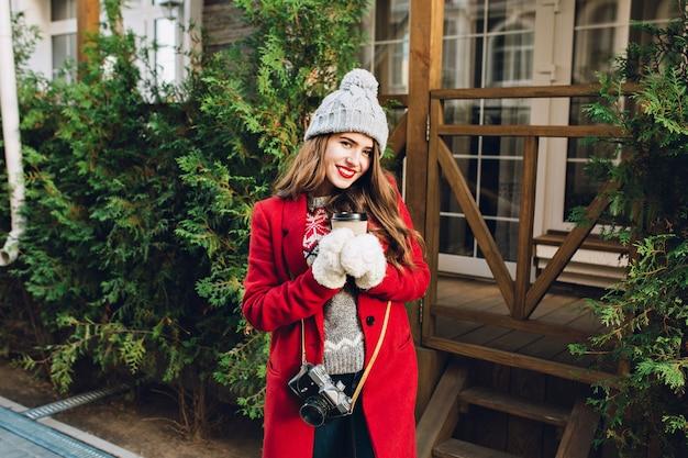 赤いコートの長い髪と木造住宅のニット帽子の美しい少女。彼女は優しい笑顔で白い手袋で行くためにコーヒーを保持しています。 無料写真