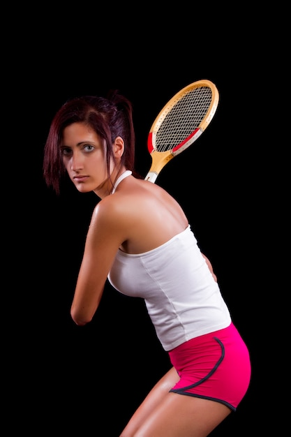 Beautiful young girl with a tennis racquet on a black background. Premium Photo