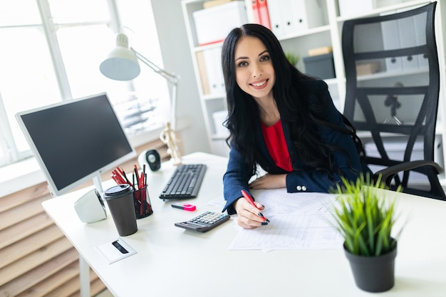 Beautiful young girl working with calculator and documents in the office at the table Premium Photo