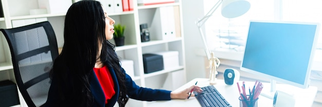 Beautiful young girl working with computer and documents in the office at the table. Premium Photo
