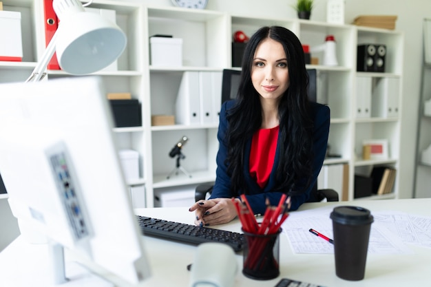Beautiful young girl working with computer and documents in the office at the table Premium Photo