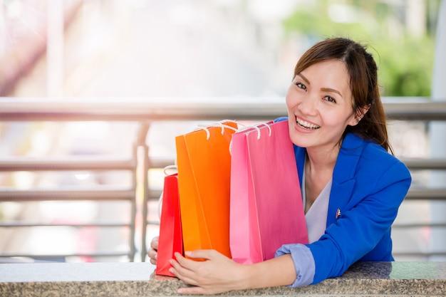 Красивые молодые девушки с разноцветными сумками на пути к торговому центру Premium Фотографии