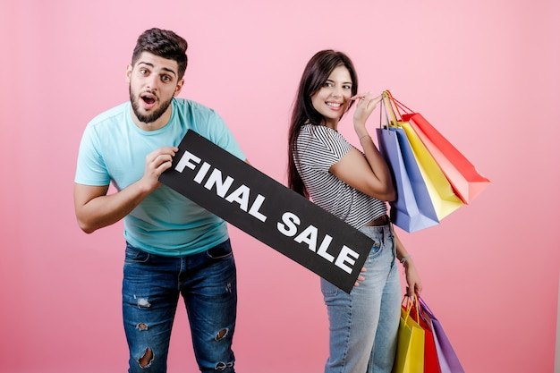 Beautiful young happy smiling couple man and woman with final sale sign and colorful shopping bags Premium Photo