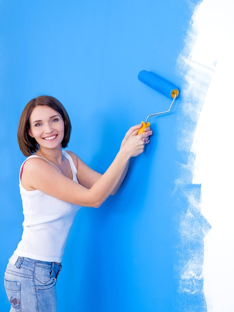 Beautiful young happy woman brushing the wall Free Photo