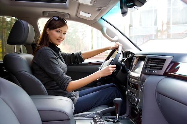 새 차 안에서 포즈를 취하는 아름 다운 젊은 행복 한 여자 무료 사진