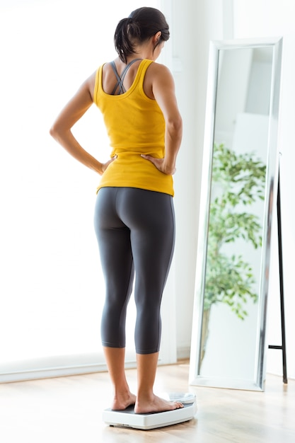 Beautiful young healthy woman on home scales. Free Photo