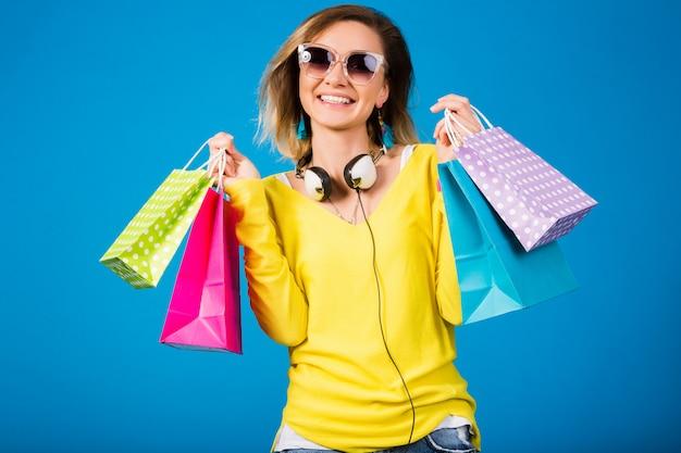 Красивая молодая хипстерская женщина, держащая красочные бумажные хозяйственные сумки Бесплатные Фотографии