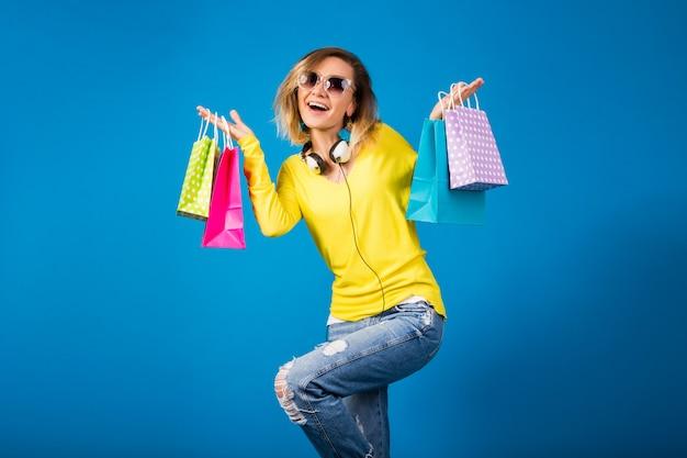 カラフルな紙の買い物袋を保持している美しい若い流行に敏感な女性 無料写真