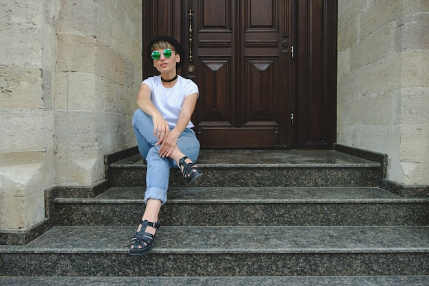 Beautiful young hipster woman posing sitting on stairs Free Photo