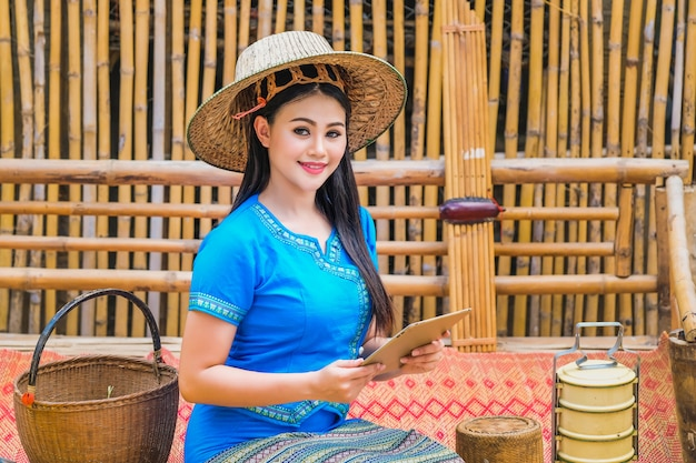 Beautiful young lady in a traditional thai dress with a tablet to receive customer orders. Premium Photo