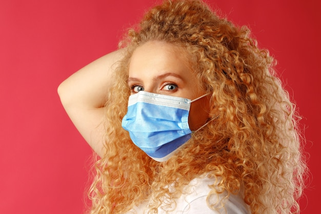 医療用フェイスマスクを身に着けている巻き毛の美しい若い女性 Premium写真