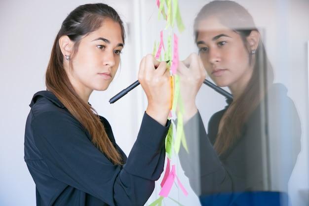 Bella giovane imprenditrice latina scrivendo su adesivo con pennarello. responsabile femminile professionale concentrato che condivide l'idea per il progetto e che prende nota Foto Gratuite