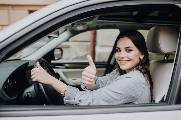 Bella giovane donna latina che guida la sua automobile nuova di zecca e che mostra il suo pollice in su Foto Gratuite