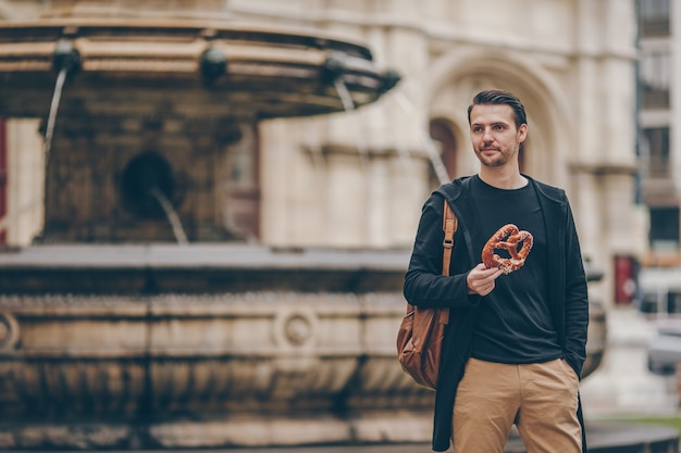 Beautiful young man holding pretzel and relaxing in park Premium Photo