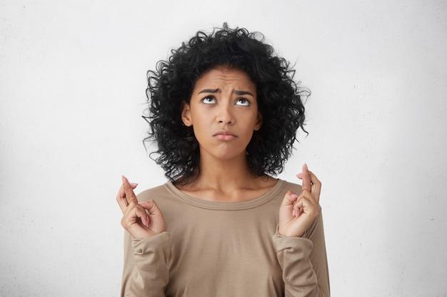 Красивая молодая студентка смешанной расы в футболке с длинными рукавами, скрестив пальцы Бесплатные Фотографии
