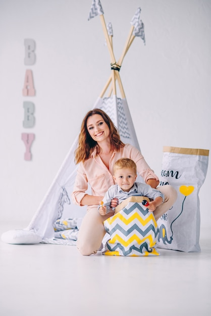 A Beautiful Young Mom And Her Little Son Having Fun In The Light