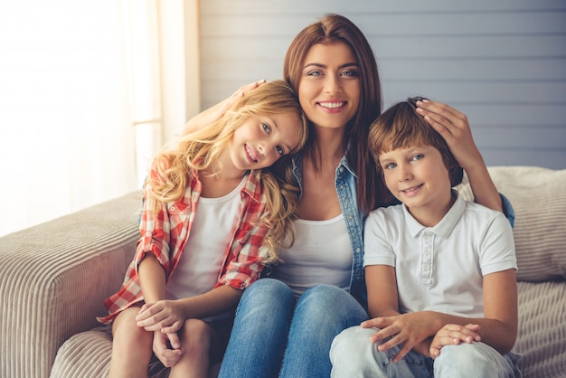 Beautiful young mother and her children are hugging. Premium Photo