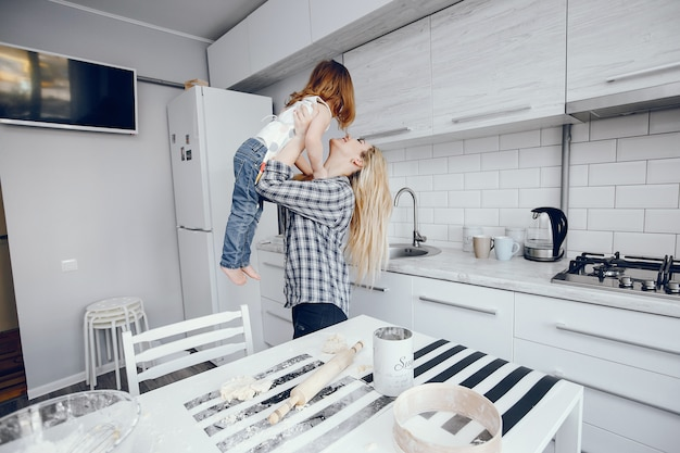 A beautiful young mother with her little daughter is cooking in the kitchen at home Free Photo